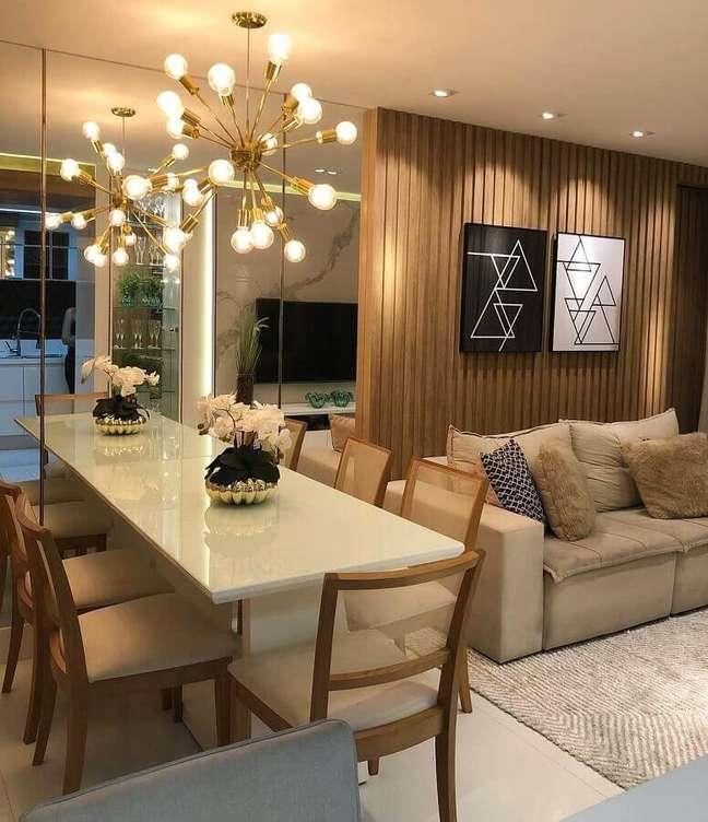 40. Lustre moderno para sala de estar e jantar integrada decorada com painel ripado de madeira – Foto: De Paula e Nobrega