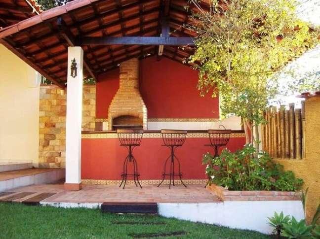 12. Banquetas estilosas e parede vermelha decoram a área da edícula simples. Fonte: Jeito de Casa