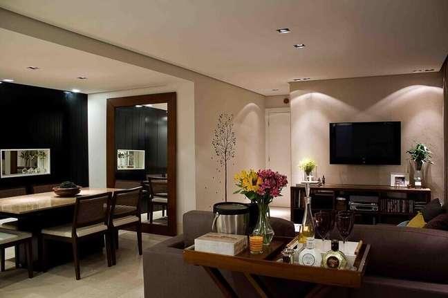 50. Sala de estar e jantar integrada decoradas com espelho de parede grande e aparador barzinho – Foto: Karen Pisacane