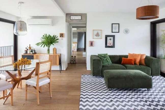 49. Projeto sala de estar e jantar integradas decoradas com sofá verde e mesa redonda de vidro – Foto: MPA Arquitetos