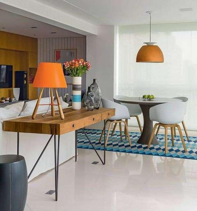 18. Decoração de sala de estar e jantar integrada com aparador de madeira e luminária redonda – Foto: Casa Pensada