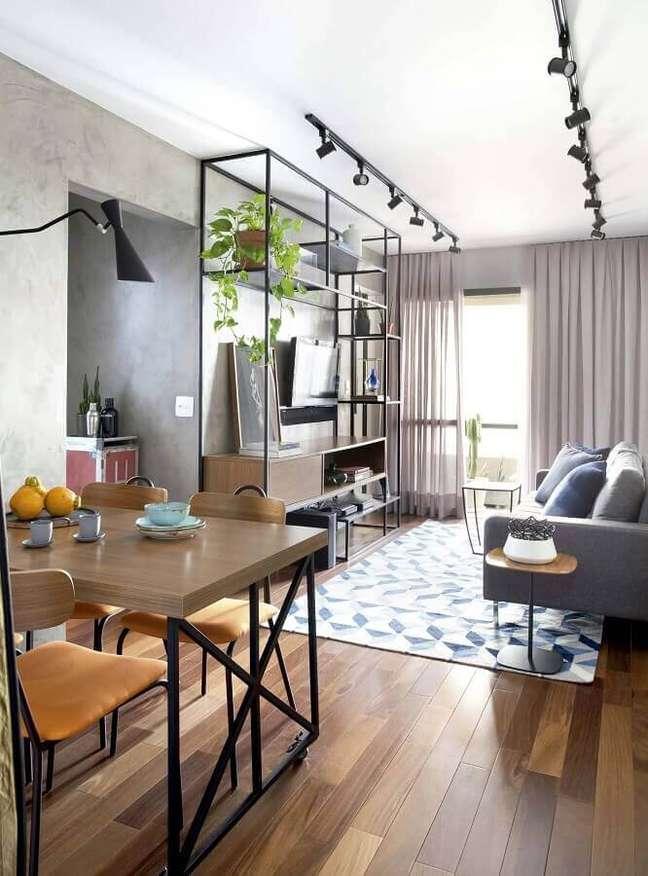 38. Decoração estilo industrial com trilho de luz para sala de estar e jantar integrada – Foto: Mandril Arquitetura + Interiores