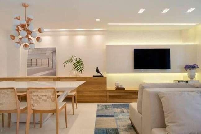 5. Sala de estar e jantar integradas modernas decoradas em cores claras com cadeira de palha e tapete cinza e azul mesclado – Foto: Leila Dionizios Arquitetura