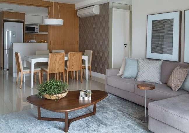 21. Decoração de sala de estar e jantar integrada com sofá cinza e mesa de centro diferente – Foto: Ana Yoshida