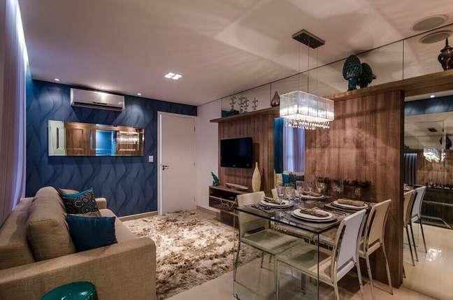 34. Papel de parede azul e tapete felpudo para decoração de sala de estar e jantar integrada – Foto: Blog da MRV