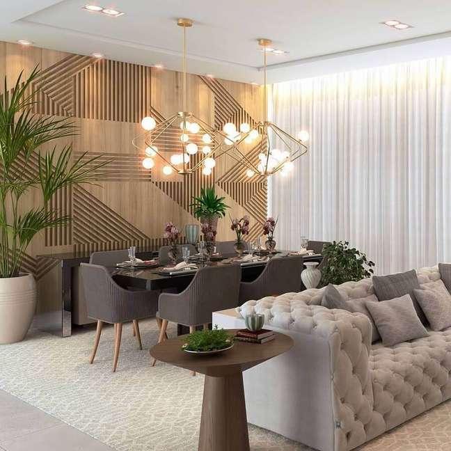 53. Sala de estar e jantar integradas modernas decoradas com sofá cinza capitonê e parede 3D de madeira – Foto: Katia Lopes