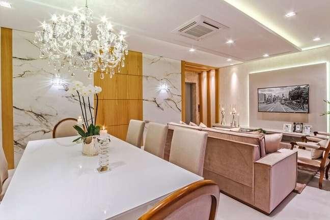 11. Cores neutras para decoração sofisticada de sala de jantar e estar integradas com lustre de cristal – Foto: Decor Salteado