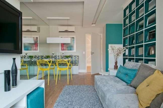 8. Cadeira amarela para decoração de sala de estar e jantar integrada azul e cinza – Foto: Adriana Fontana