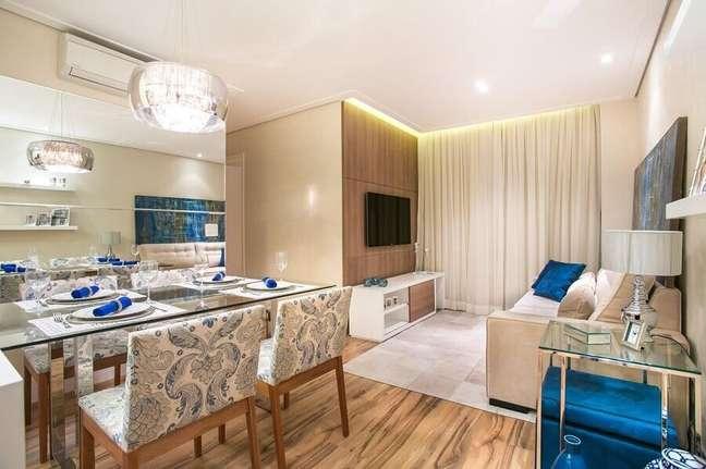 33. Decoração de sala de estar e jantar integradas com mesa de vidro e piso de madeira – Foto: Carolina Bernardi