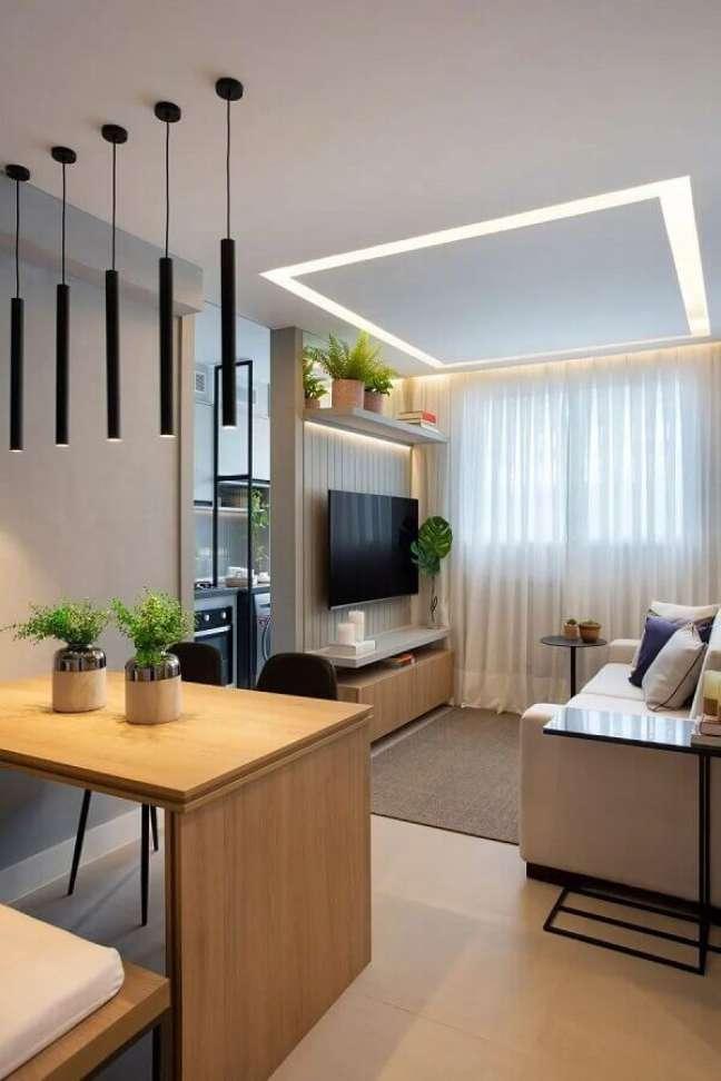 6. Sala pequena decorada com luminária pendente e prateleira para plantas – Foto: Bianca da Hora