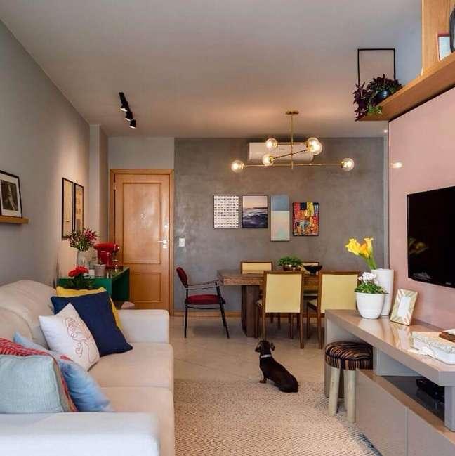 51. Sala de estar e jantar integrada decorada com parede de cimento queimado e lustre moderno – Foto: Decor Fácil