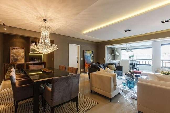 39. Lustre de cristal para decoração de apartamento com sala de estar e jantar integrada – Foto: Orlane Santos