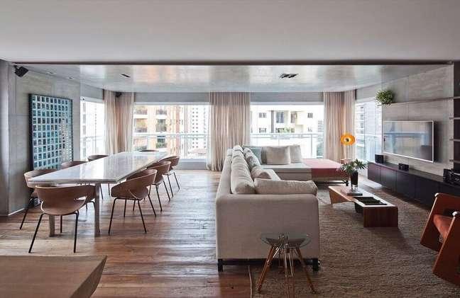 20. Decoração de sala de estar e jantar integrada com parede de cimento queimado e mesa grande – Foto: Carpintaria Rezende