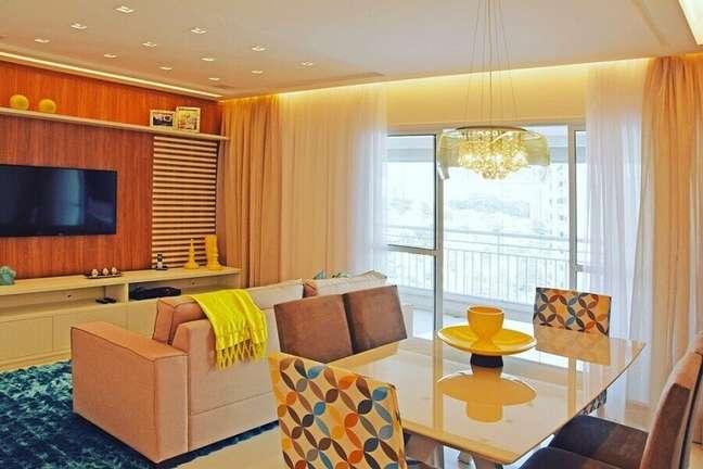 16. Decoração de apartamento com tapete azul e cadeiras coloridas para sala de estar e jantar integrada – Foto: Carlos Franscisco