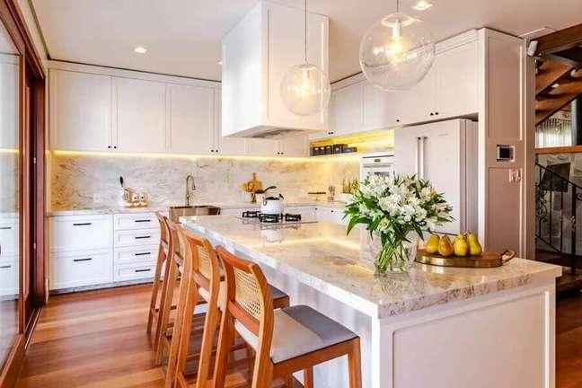 19. Banqueta de madeira para decoração clássica de cozinha planejada com ilha toda branca – Foto: Incomum Arquitetura Singular