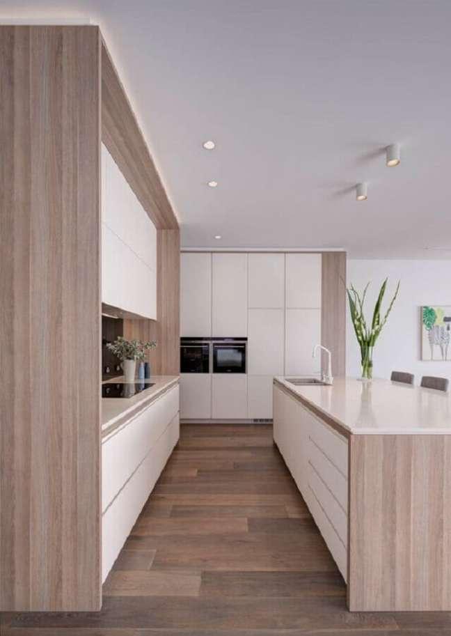 40. Decoração em cores claras para cozinha planejada grande com ilha com detalhes em madeira – Foto: Taylor Pressly Architects