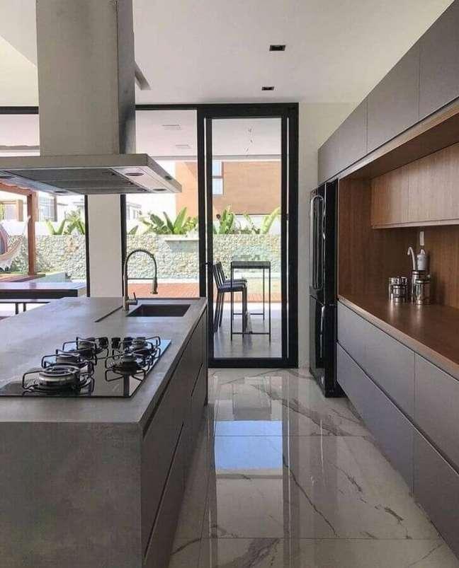 10. Armário cinza com madeira para decoração moderna de cozinha planejada com ilha gourmet de concreto – Foto: Tatyane Severiano