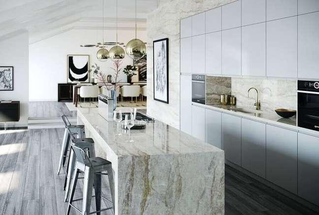 30. Cozinha planejada grande com ilha de mármore decorada com luminária pendente redonda – Foto: Cosentino