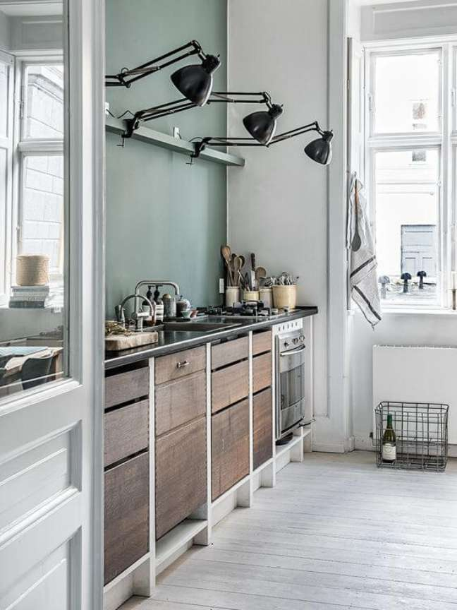 9. Cozinha com armários de madeira e parede verde sage – Foto Aiayu