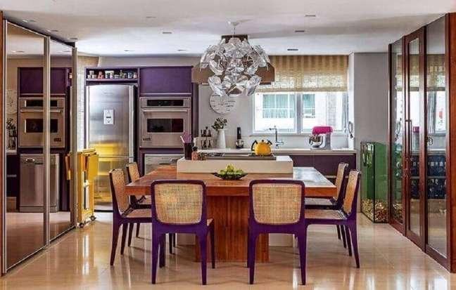 58. Lustre moderno para decoração de cozinha planejada com ilha e bancada de madeira com cadeiras roxas – Foto: Maricy Borges