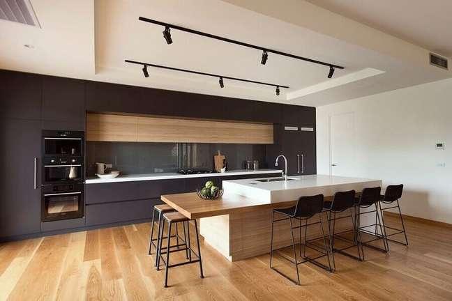 51. Decoração moderna de cozinha planejada grande com ilha branca e bancada de madeira – Foto: Houzz