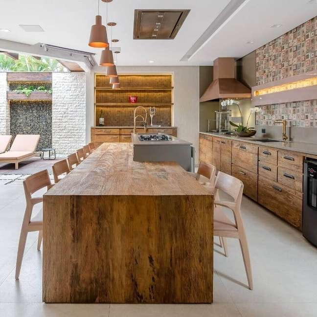 59. Mesa de madeira rustica para decoração de cozinha com ilha planejada – Foto: Okha Arquitetura