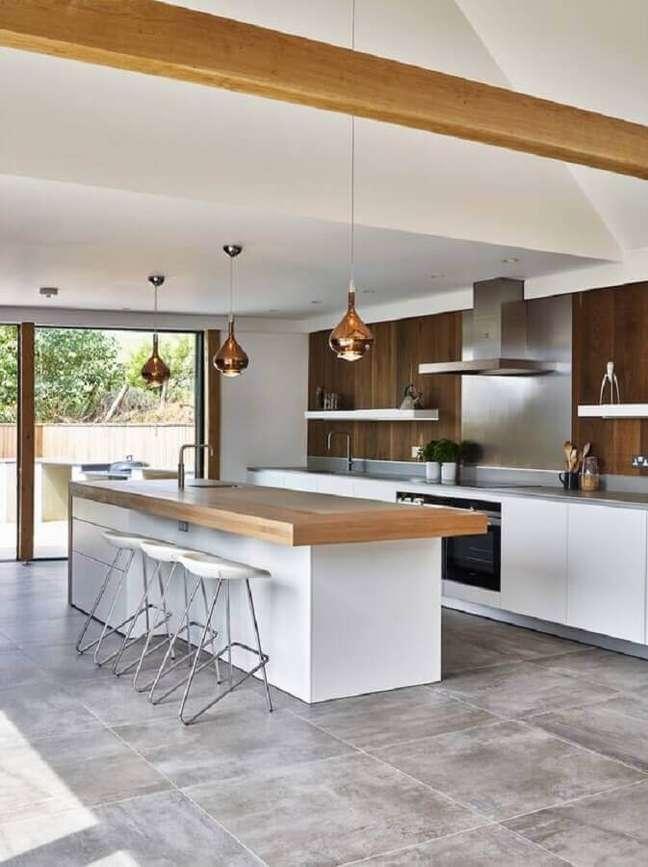 31. Cozinha planejada grande com ilha decorada com bancada de madeira e luminária cobre – Foto: Houzz