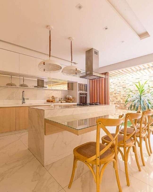 22. Cadeira de madeira para cozinha planejada com ilha no meio com decoração em cores neutras – Foto: Studio4