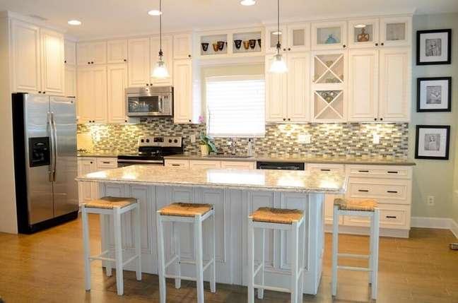 28. Cozinha planejada com ilha no meio decorada em estilo clássico – Foto: Beach home makeover