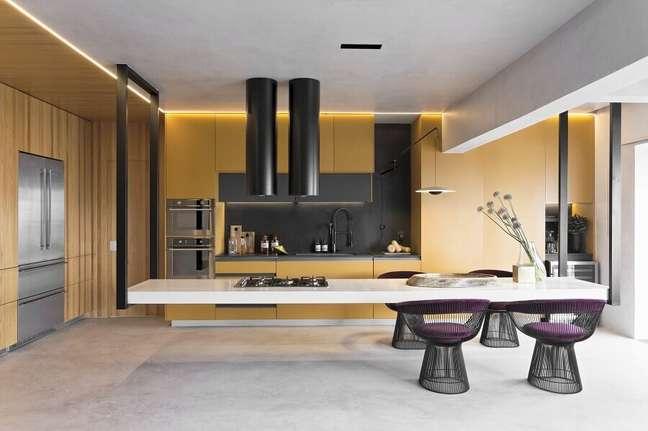 26. Cozinha planejada com ilha moderna decorada com armários amarelos e cadeira estofada – Foto: Diego Revollo