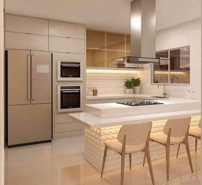 39. Decoração em cores claras com revestimento 3D para cozinha com ilha planejada – Foto: Catia Porcino