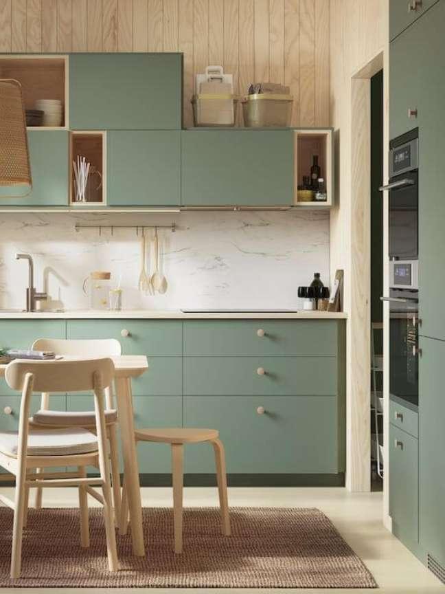 44. Armários de cozinha verde sage com revestimento marmorizado e detalhes em madeira – Foto Ikea