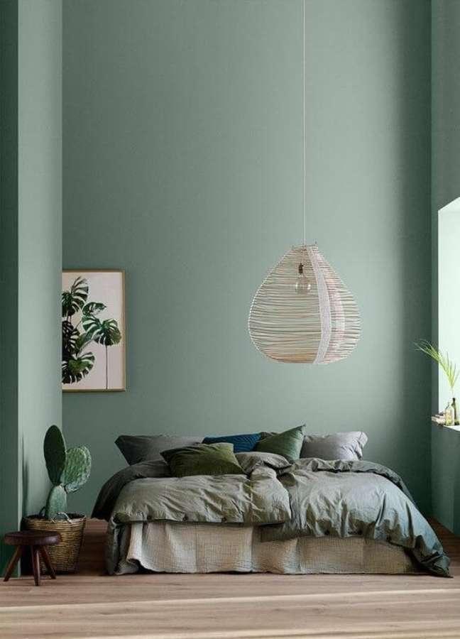 28. Quarto com parede verde sage e roupa de cama combinando – Foto Revista Arquitectura y Diseno