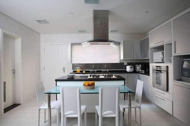 9. Armário branco para decoração clean de cozinha planejada com ilha no meio e bancada de vidro – Foto: Claudia Arakaki