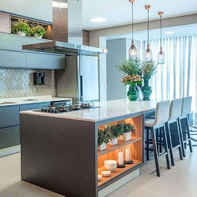 27. Cozinha planejada com ilha moderna decorada com luminária de vidro e nichos com iluminação – Foto: Houzz