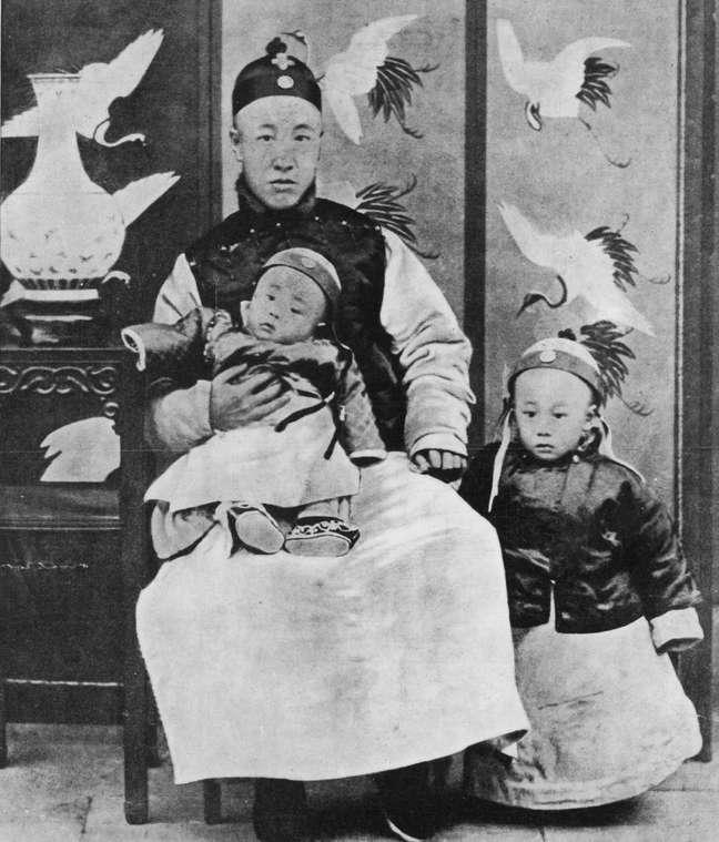 1909: Príncipe Chun, regente e controlador da nação, com seu filho mais novo ajoelhado e Puyi (1906-1967), Imperador da China, ao seu lado