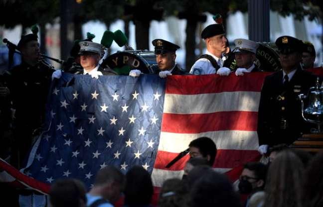 Policiais e bombeiros seguram bandeira dos EUA em cerimônia pelos 20 anos dos atentados de 11 de setembro, em Nova York