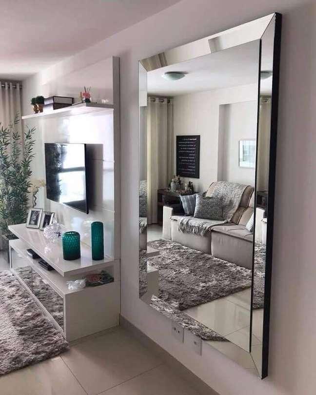 31. Espelho grande na sala de estar branca decorada com tapete felpudo e painel para TV – Foto: Art + Moveis Espelhados