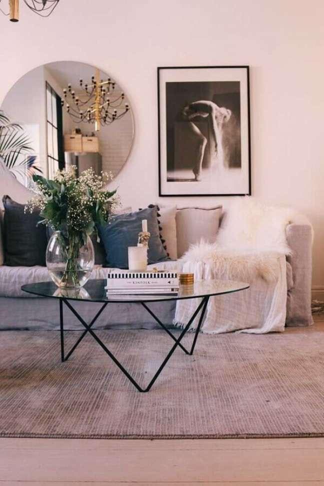 1. Espelho redondo na sala de estar decorada com sofá cinza e mesa de centro de vidro – Foto: Decor Fácil
