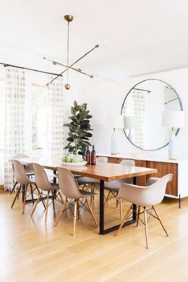 13. Decoração clean com lustre moderno e espelho redondo na sala de jantar – Foto: MyDomaine
