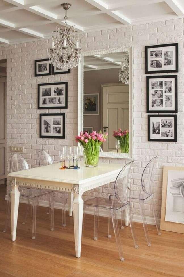 50. Espelho na sala pequena decorada com parede tijolinho branca e cadeiras transparentes – Foto: FresHOUZ