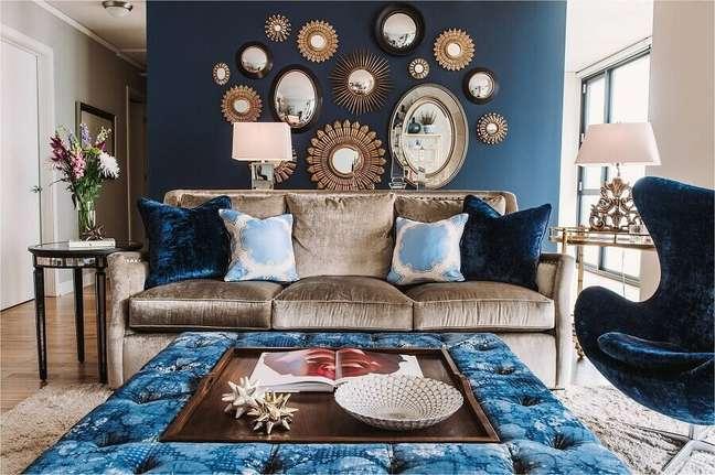 7. Parede com espelho na sala de estar azul decorada com sofá marrom – Foto: Design Homes