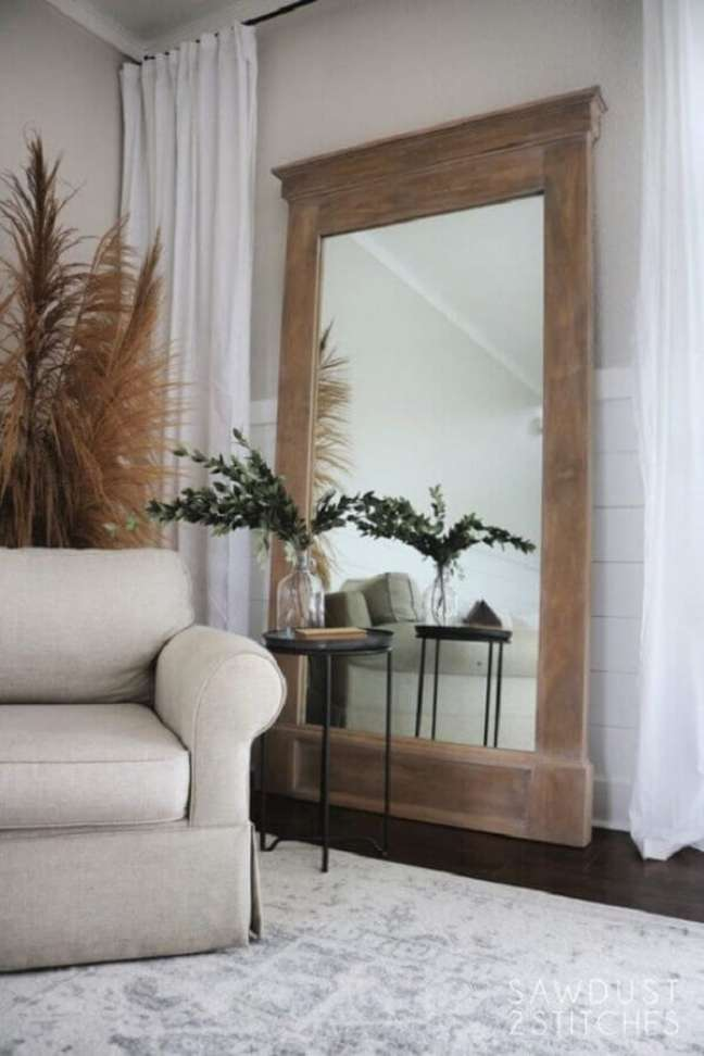 32. Espelho grande na sala de estar decorada com poltrona bege e mesa lateral redonda – Foto: Sawdust 2 Stitches