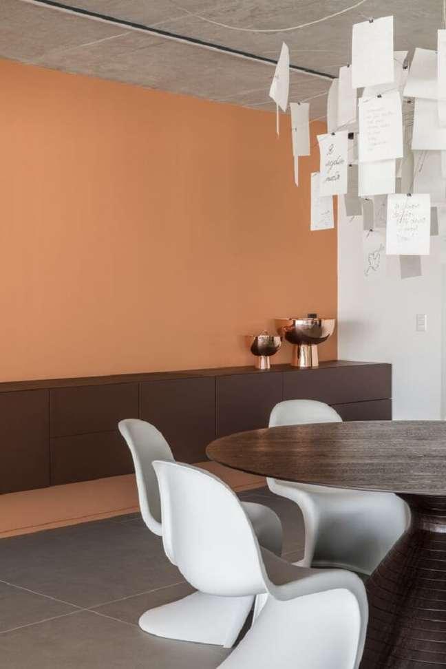 3. Buffet de madeira suspenso, mesa de jantar redonda e cadeiras Panton marcam o décor da sala de jantar. Foto: Studio Julliana Camargo