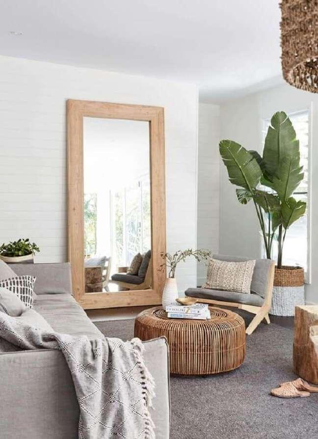 36. Espelho na sala de estar cinza e branca decorada com poltrona de madeira e vaso de planta no chão – Foto: Apartment Therapy