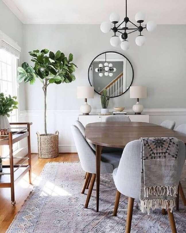 57. Parede com espelho na sala de jantar decorada com lustre moderno e cadeiras estofadas – Foto: Apartment Therapy