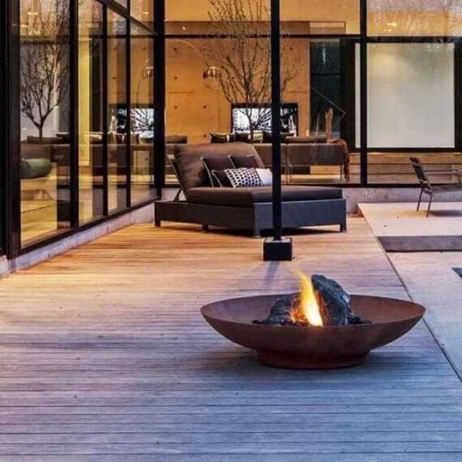 9. Chaise área externa com lareira perto e piso de madeira – Foto Americanas
