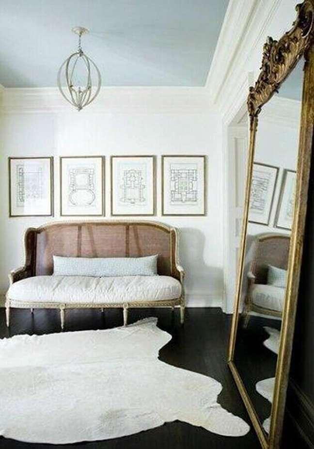 35. Espelho grande na sala decorada com sofá antigo e tapete branco – Foto: Architecture Art Designs