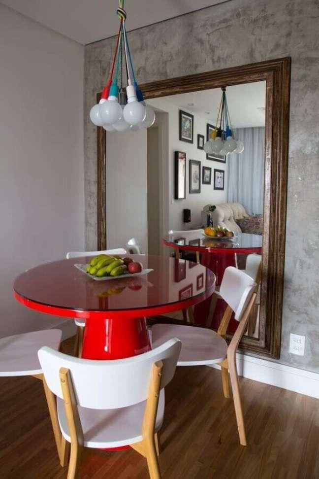 33. Espelho grande na sala de jantar decorada com mesa redonda vermelha e parede de cimento queimado – Foto: Decor Fácil