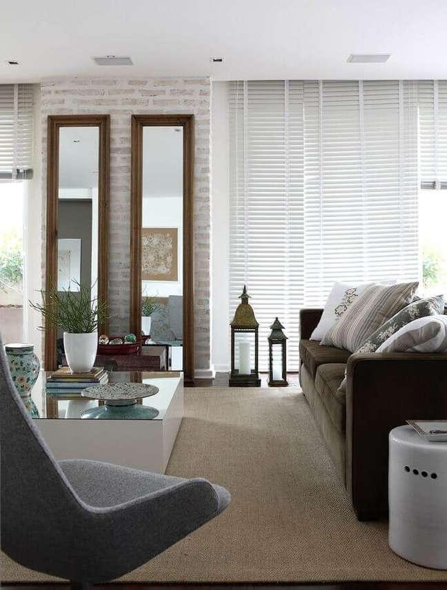 39. Espelho na sala de estar grande decorada com sofá marrom e parede tijolinho – Foto: Caroline Gabriades